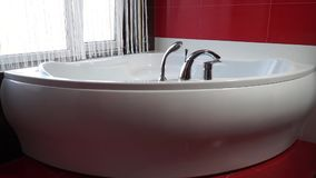 Zoom a white bath in red bathroom. Zoom to beautiful large white bath in red bathroom stock video