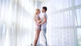 Zoom in of young lovers in pajamas hugging in morning sunshine near big window. Zoom in of young lovers in pajamas hugging in morning sunshine near big curtained stock video
