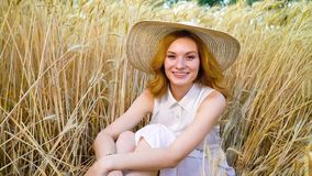 Zoom in of young romantic red haired woman smiling at camera in wheat field. Zoom in of young romantic red haired woman smiling at camera sitting in wheat field stock video