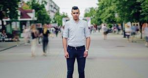 Zoom za czasu upływie atrakcyjna mieszana biegowa facet pozycja w ulicie wśród tłumu zbiory wideo