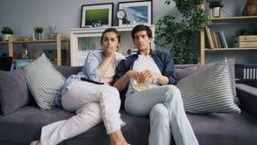 Zooma in av den unga familjen som håller ögonen på ledsen film på TV som hemma äter popcorn stock video