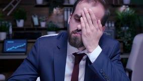 Zooma i skott av den trötta och utmattade affärsmannen som sent arbetar - natt i kontoret lager videofilmer
