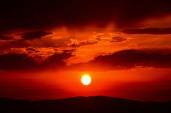 Zoomed in Orange Sunset. With sun and soft light rays visible through dark cloud cover Stock Image