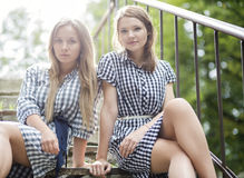 Zoomed womans in dresses sit on stairs Royalty Free Stock Photo