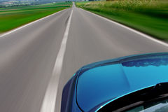 Zooming car. Blue car zooming fast down the highway road with motion blur Royalty Free Stock Photos