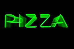 Zooming Green Neon Pizza Sign. Blurred Green Neon Pizza Sign for Zooming Lens During Exposure on Black, Copy Space Royalty Free Stock Image