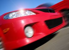Zooming Mazda. Zooming red Mazda car on a sunny day Stock Image