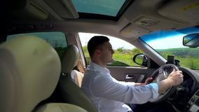 Zooming in onto the male driver of a car. Zooming in through the open passenger window onto the young male driver of a car clutching the steering wheel with stock footage