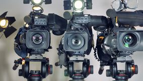 A zooming in shot on three video cameras. stock video footage