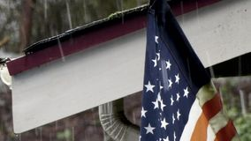 Zooming in on snow falling in winter on american flag and roofline. American flag draped from house roof in winter with snow stock footage