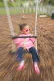 Zooming on a Swing. A zoomed shot of a young girl on a swing wearing pink sunglasses Stock Images