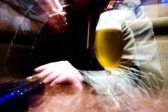 Zooming to bier. Lens zooming to drunk man behind Glass of beer Royalty Free Stock Photo