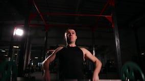 Zoomkamera mannen utför att lyfta stången i idrottshallen kameran flyttar sig framåtriktat och tillbaka arkivfilmer