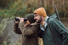 Zoon die door verrekijkersvader status kijken stock fotografie
