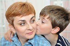 Zoon die en zijn moeder koesteren kussen Stock Foto's