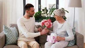 Zoon die heden en bloemen geven aan hogere moeder stock footage