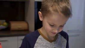 Zoon die mamma in de keuken helpen, schilderen zij een gelukkige gezichtsbloem Voorbereiding van bollen, traditionele Oekraïense  stock videobeelden