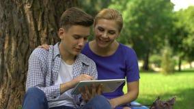 Zoon die mamma tonen hoe te om bankwezen en loonsrekeningen via tablet, moderne technologie te gebruiken stock footage