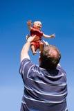 Zoon die omhoog in lucht door papa wordt geworpen Stock Foto