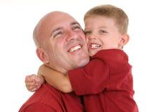 Zoon die Papa koestert rond de Hals Stock Foto