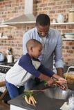 Zoon die Vader To Prepare Vegetables voor Maaltijd in Keuken helpen Stock Afbeeldingen