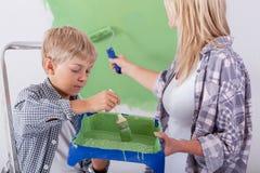Zoon die zijn moeder helpen die een muur schilderen Royalty-vrije Stock Afbeelding
