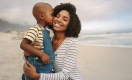 Zoon die zijn moeder kussen bij het strand royalty-vrije stock afbeelding