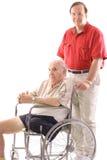 Zoon die zijn vader in een rolstoel duwt Royalty-vrije Stock Foto