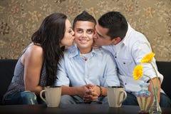 Zoon door Ouders wordt gekust die royalty-vrije stock afbeeldingen