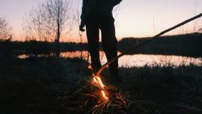 Zoon en papa door de brand, voeten close-up familie die op riverbank bij nacht kamperen stock footage