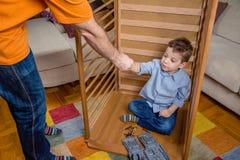 Zoon en vader het assembleren wieg voor pasgeboren bij Stock Foto