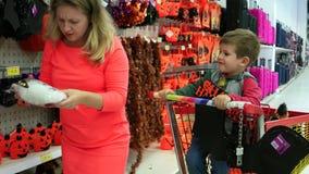 Zoon in het boodschappenwagentje met haar moeder in een supermarkt, moeder en zoon die voor de Vooravond van Al Hallows, Hallowee stock video