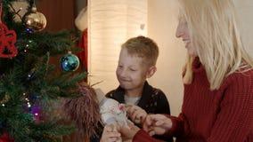 Zoon het spelen met hand - gemaakte pop onder Kerstmisboom stock footage