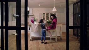 Zoon het verrassen moeder met bloemen in keuken stock videobeelden