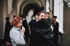 zoon omhelzingen ouders Gelukwensen student royalty-vrije stock afbeelding