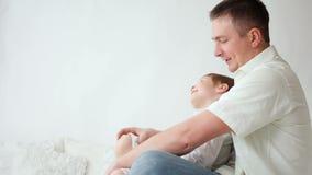 Zoonsspelen met papa thuis op het bed stock videobeelden