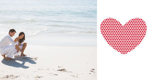 Złożony wizerunek rysuje serce w piasku śliczna para Zdjęcia Royalty Free