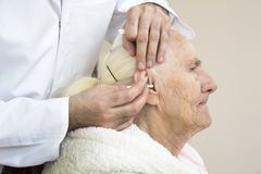 Zorg en verzorging van oude mensen Het schoonmaken van de oren met een stok royalty-vrije stock foto's