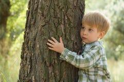 Zorg voor aard - weinig jongen omhelst boom Stock Foto