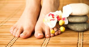 Zorg voor mooie vrouwenbenen met bloem Royalty-vrije Stock Fotografie