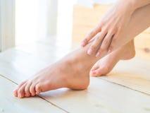 Zorg voor mooie vrouwenbenen op de vloer Royalty-vrije Stock Foto's