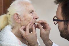 Zorgbehandelingen op het gezicht van een oude vrouw Het verwijderen van gezichtshaar met pincet royalty-vrije stock foto's