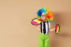 Zorgeloze kinderen Portret van gelukkige clownjongen die groot n dragen stock foto