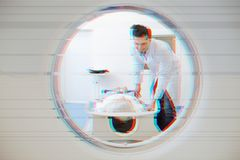 Zorgvuldige arts die en MRT in zijn kliniek glimlachen leiden stock afbeelding