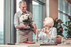 Zorgvuldige mens die bloemen geven aan een teruggetrokken dame royalty-vrije stock fotografie