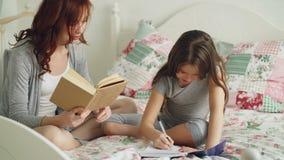 Zorgvuldige moeder die haar helpen weinig leuke dochter met thuiswerk voor basisschool Houdend van mamma een boek lezen en meisje stock videobeelden