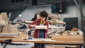 Zorgvuldige timmerman die stuk van hout bekijken die dan het oppoetsen met schuurpapier stock videobeelden