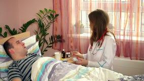 Zorgvuldige vrouw geduldige de man van de artsencontrole temperatuur met digitale thermometer stock footage