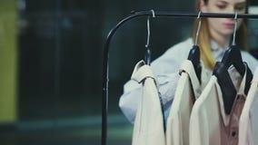 A zorra disparada da mulher consulta blusas em ganchos video estoque