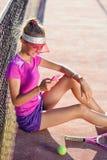 A zorra disparou da menina desportiva que senta-se em um campo de t?nis perto da rede e usa o telefone esperto conversando e surf imagens de stock